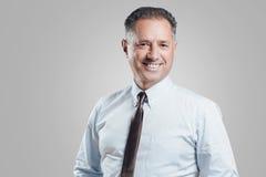 Attraktiv stående för affärsman på grå bakgrund Royaltyfria Foton