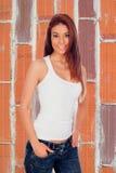 Attraktiv stads- flicka på tegelstenväggen Arkivfoton