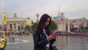 Attraktiv stilfull flicka, i ett svart omslag som ler och använder en mobiltelefon stock video