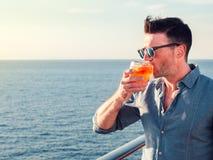 Attraktiv stilfull man i solglasögon som rymmer ett exponeringsglas av den härliga rosa coctailen arkivbilder