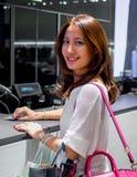 Attraktiv, stilfull trendig ung asiatisk kvinnashopping och betala på kassörskans räknare Fotografering för Bildbyråer