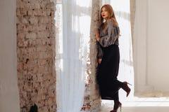 Attraktiv stilfull ung flicka nära fönstret i ljus inre arkivbilder
