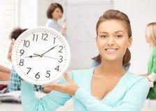 Attraktiv student som pekar på klockan Arkivbilder