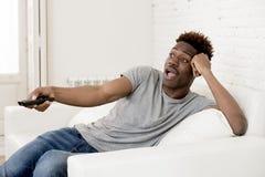 Attraktiv svart afrikansk amerikanman som sitter hållande ögonen på television för hemmastadd soffasoffa arkivbild