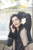 Attraktiv svart haired kvinna som använder telefonen Royaltyfri Foto