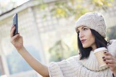 Attraktiv svart haired kvinna som använder telefonen Fotografering för Bildbyråer
