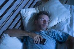 Attraktiv trött man i säng som sovande faller, medan genom att använda mobiltelefonen som rymmer fortfarande det cell- i hans han royaltyfri bild