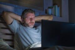 Attraktiv trött och stressad arbetsnarkomanman som sent arbetar - natten som evakueras på säng som är upptagen med den sömniga bä arkivbilder