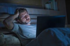 Attraktiv trött och stressad arbetsnarkomanman som sent arbetar - natten som evakueras på säng som är upptagen med den sömniga bä fotografering för bildbyråer