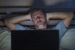 Attraktiv trött och stressad arbetsnarkomanman som sent arbetar - natten som evakueras på säng som är upptagen med den sömniga bä arkivfoto