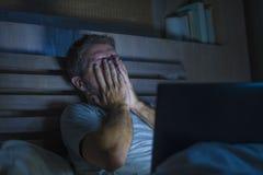 Attraktiv trött och stressad arbetsnarkomanman som sent arbetar - natten som evakueras på säng som är upptagen med den sömniga bä royaltyfria foton