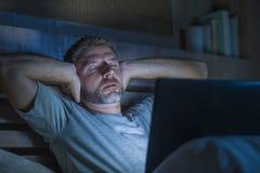 Attraktiv trött och stressad arbetsnarkomanman som sent arbetar - natten som evakueras på säng som är upptagen med den sömniga bä arkivbild