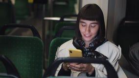 Attraktiv transport för ung kvinna offentligt genom att använda en mobiltelefon Hon är att smsa som kontrollerar poster, pratstun stock video