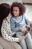 Attraktiv trevlig moder som håller ögonen på en video med en dotter royaltyfria foton