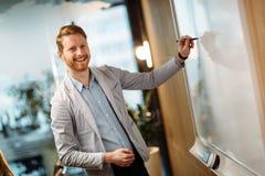 Attraktiv ung affärsman som i regeringsställning gör presentation arkivbilder