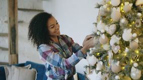 Attraktiv ung afrikansk kvinna som dekorerar hemmastatt förbereda sig för julgran för Xmas-beröm royaltyfri bild