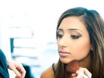 Attraktiv ung asiatisk indisk kvinna som har hennes smink att göras Arkivfoto