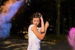 Attraktiv ung asiatisk kvinna med långt hår som spelar med Holi po Fotografering för Bildbyråer