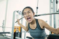 Attraktiv ung asiatisk kvinna som utarbetar med övningsmaskinen på idrottshallen fotografering för bildbyråer