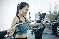 Attraktiv ung asiatisk kvinna som utarbetar med övningsmaskinen på idrottshallen arkivbilder