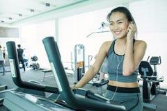 Attraktiv ung asiatisk kvinna som utarbetar med övningsmaskinen på idrottshallen royaltyfri foto