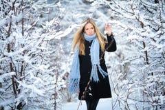 Attraktiv ung blond flicka som går i nätt kvinna för vinterskog i utomhus- vintertid Bärande vinterkläder Fotografering för Bildbyråer