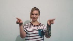 Attraktiv ung blond form för kvinnaattraktionhjärta i luft med fingrar på den vita väggen arkivfilmer
