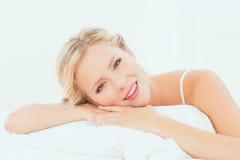 Attraktiv ung blondin som ligger på hennes säng som ler på kameran royaltyfri foto