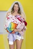 Attraktiv ung brud som bär den hållande smutsiga tvätterit som skriker med frustration Royaltyfria Foton