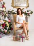Attraktiv ung dam i den vita klänningen som poserar i inre jul Royaltyfri Fotografi