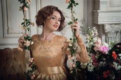Attraktiv ung dam på de blommiga gungorna horisontal Royaltyfri Fotografi