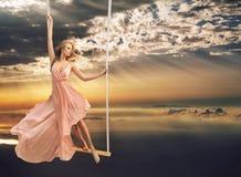 Attraktiv ung dam på en gunga ovanför havet royaltyfria foton