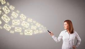 Attraktiv ung dam som rymmer en telefon med meddelandesymboler Arkivbilder