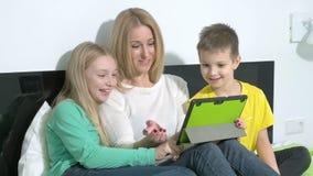 Attraktiv ung familj som använder en minnestavla för att göra framtida plan stock video