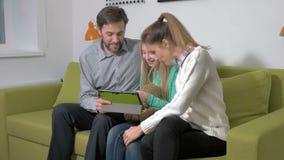Attraktiv ung familj som använder en minnestavla för att göra framtida plan arkivfilmer