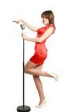 Attraktiv ung flicka i en röd klänning som sjunger in i en mikrofon royaltyfri bild