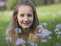Attraktiv ung flicka i en vildblommaäng Fotografering för Bildbyråer