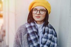 Attraktiv ung flicka i exponeringsglas i lag och gul basker p? en enkel ljus bakgrund royaltyfria foton