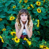 Attraktiv ung flicka i fältet av solrosor arkivfoto