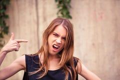 Attraktiv ung flicka med den ilskna framsidan Arkivbild