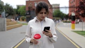 Attraktiv ung flicka med kaffe och smartphonen som går i sommargatan stock video