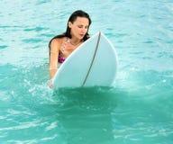 Attraktiv ung flicka på surfingbrädan i havet Arkivfoto