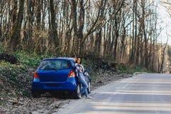 Attraktiv ung flicka på vägen nära bilen fotografering för bildbyråer