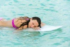 Attraktiv ung flicka på surfingbrädan i havet Fotografering för Bildbyråer