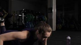 Attraktiv ung flicka som g?r ?vning ?va kondition hans vatten f?r manreflexionsutbildning Aftonutbildning i idrottshallen Push-UP lager videofilmer