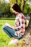 Attraktiv ung flicka som läser en bok på naturen nära träd Royaltyfri Bild