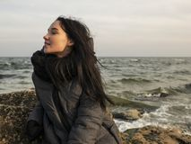 Attraktiv ung flicka som sitter på en sten nära havet på en bakgrund av grå himmel arkivbild