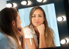 Attraktiv ung flicka som stirrar in i spegeln Fotografering för Bildbyråer