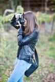 Attraktiv ung flicka som utomhus tar bilder Den gulliga tonårs- flickan i jeans och det svarta läderomslaget som tar foto parkera Fotografering för Bildbyråer