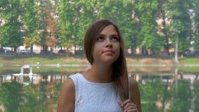 Attraktiv ung flicka som väntar på hans flickvän för en gå lager videofilmer